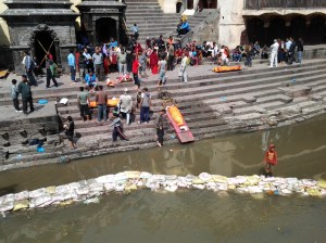 Preparing bodies (washing them in the river) for cremation.