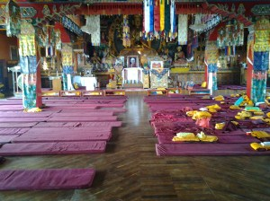 Inside the temple, with prayer mats spread on the floor.