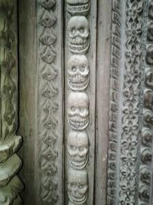 Wood door jamb with skull carvings.