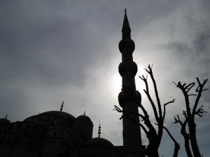 Sun partially hidden by clouds and silhouetted behind this Blue Mosque minaret.