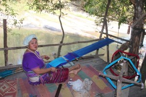 A village woman weaving clothes for her family.