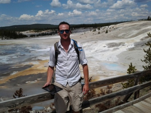 Jeremy with the mud pots and hot springs behind him.