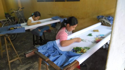 A young Vietnamese seamstress embroidering a beautiful pattern in the cloth.