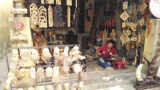 Artisan shaping wood head carvings.