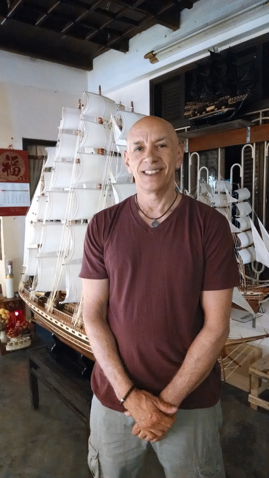 In a shop, posing near a hand made miniature clipper ship.
