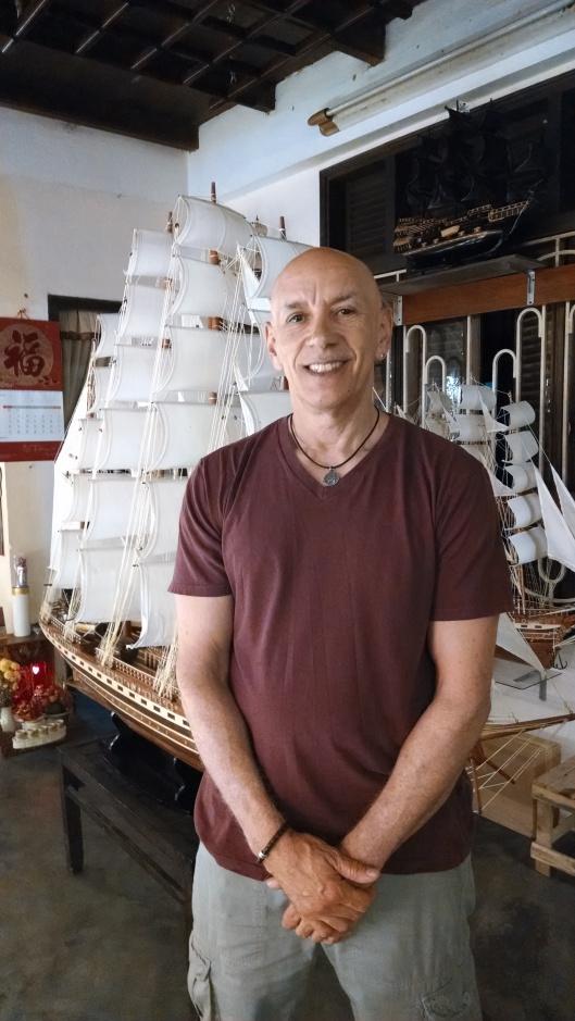 In a shop, posing near a hand made miniature clipper ship.