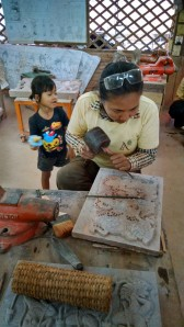 Childcare is usually provided by a relative (grandmother). However, it is not unusual for a mother to bring her child to work, as this artist has done.