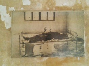 "Photo taken of one of the last victims interrogated, tortured, and killed at Tuol Sleng. When the Vietnamese routed the Cambodian capital of Phnom Penh, they found this victim, still chained to the ""bed"" used for securing a prisoner while he was questioned and tortured."