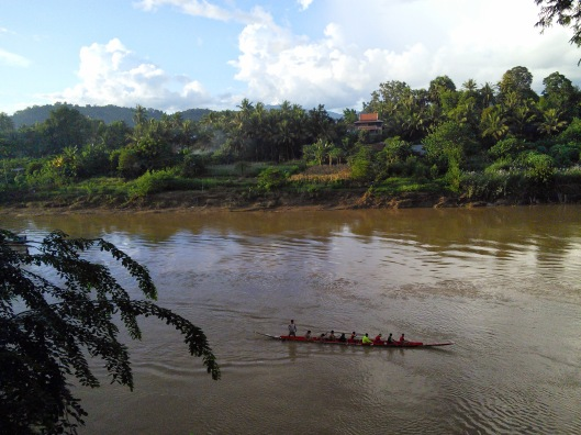 "The following images are of the river and particularly of a rowing team practicing their skils. The young men would ""sing"" motivational Lao songs to keep their rowing in rhythm."