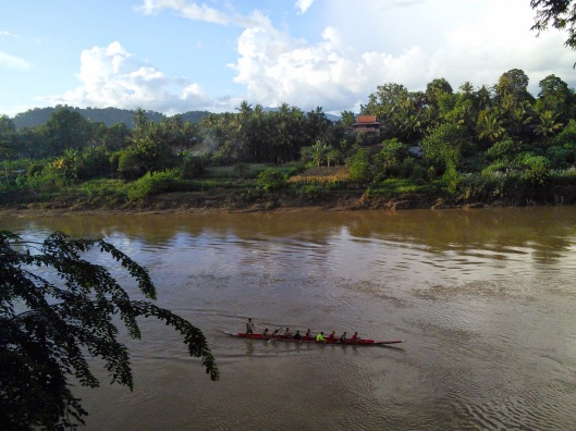 Rowing team practicing their skills on the river. They would sing in unison to motivate themselves to row faster and in rhythm.